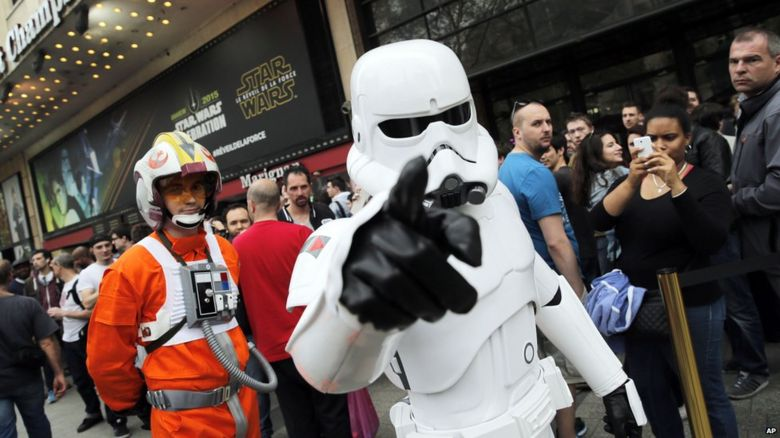 A man dressed as a Stormtrooper walks past people as they queue to attend the steaming of Star Wars Celebration