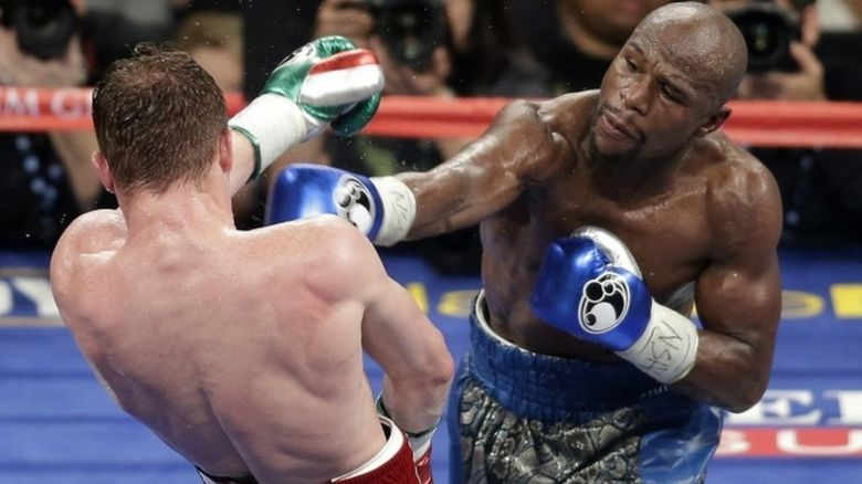Floyd Mayweather Jr., right, throws a punch against Canelo Alvarez