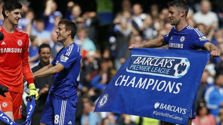 Gary Cahill holds a flag reading champions