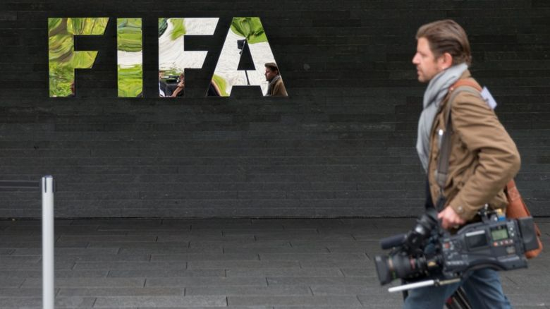 cameraman walks past a fifa logo