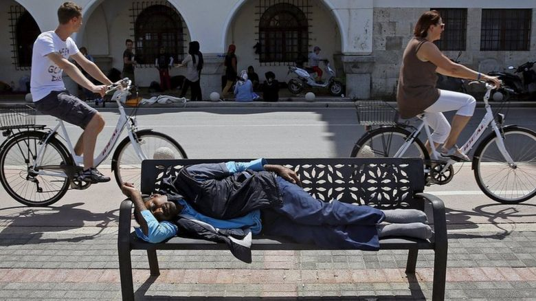A migrant sleeps on a bench and others gather on the side of the road as two people cycle passed