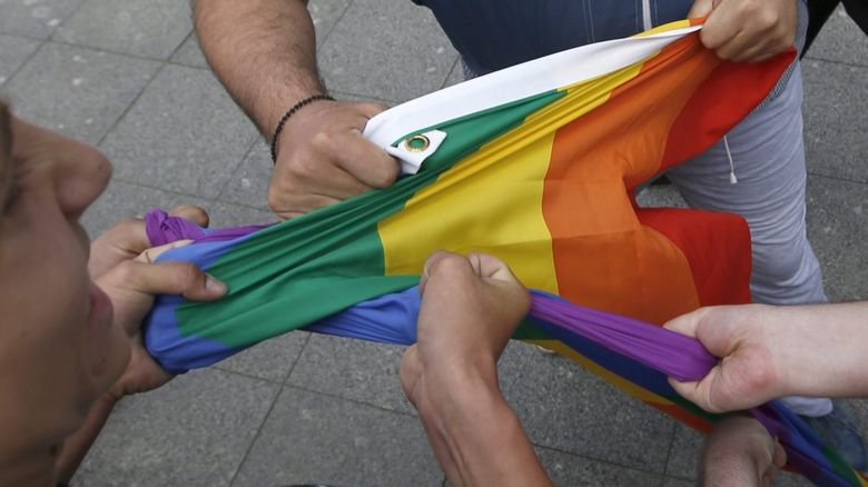 Hands grabbing a rainbow flag