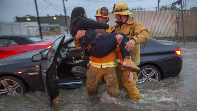 A firefighter carries a woman from her car after it was caught in street flooding in southern California.