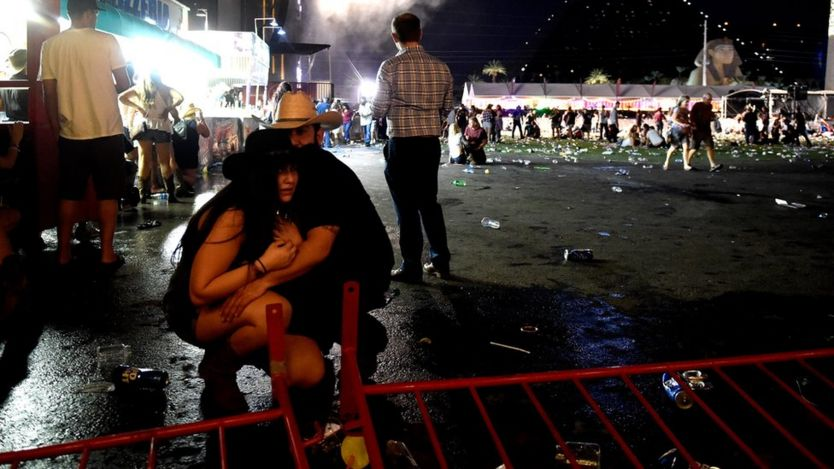 A couple, wearing country music hats, cower together at the scene of a shooting at musical festival