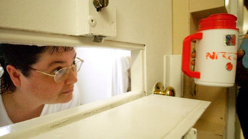 Kelly Gissendaner looks through the slot in her cell door as a guard brings her a cup of ice.