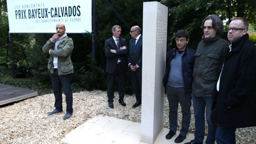 French cartoonist Riss (2nd R) stands alongside the general secretary of NGO Reporters Sans Frontieres (RSF) Christophe Deloire (1st R) and financial director of the satirical magazine Charlie Hebdo, Eric Portheault (3rd R), during the unveiling of a stone in honour of the war reporters killed in 2015 in the war reporters' memorial, on 8 October 2015 in Bayeux, north-western France, during the annual Bayeux-Calvados war journalism award week