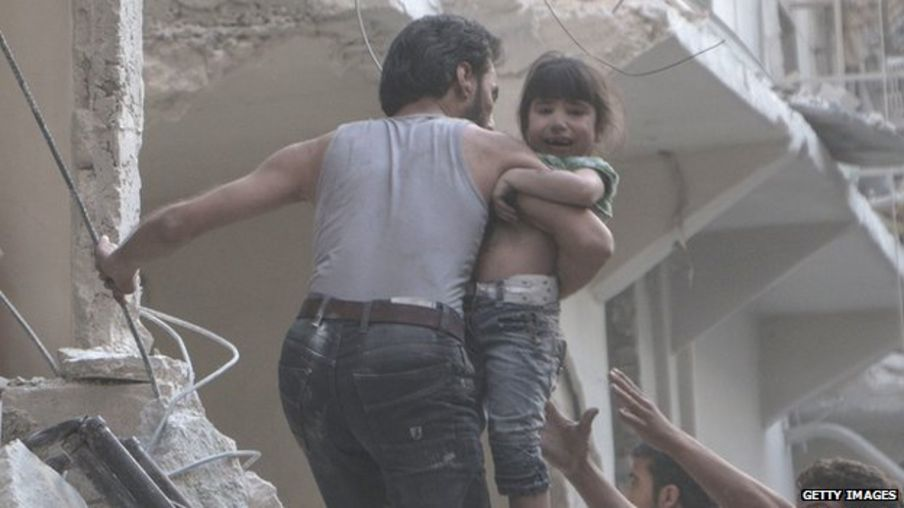 A man evacuates a child from a building following a reported barrel bomb attack by Syrian government forces on the northern Syrian city of Aleppo, on May 30, 2015. Barrel bombs dropped from regime helicopters killing more than 70 civilians in Aleppo, while government forces in neighbouring Iraq retook an area west of the jihadist-controlled city of Ramadi. AFP PHOTO / KARAM AL-MASRI