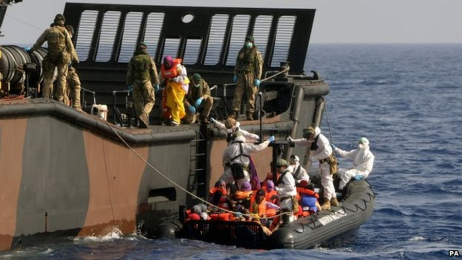 HMS Bulwark staff help refugees adrift in the Mediterranean onto a Royal Navy Landing Craft in the Mediterranean taken on 7 May 2015
