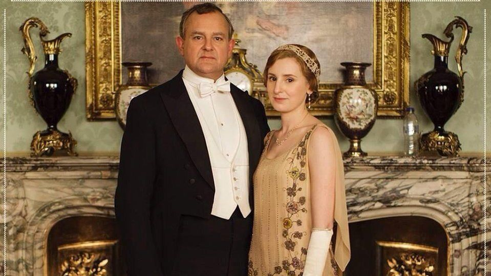 The Early of Grantham and Lady Edith standing in front of a shelf with a bottle on