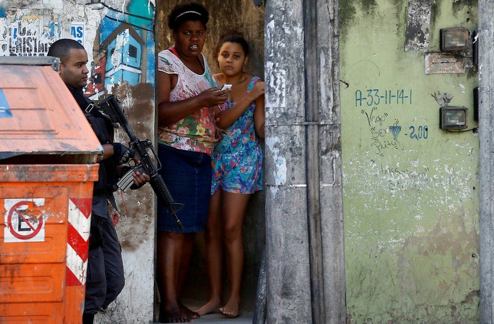 A policeman takes position during an operation against drug dealers in Cidade de Deus or City of God slum in Rio de Janeiro