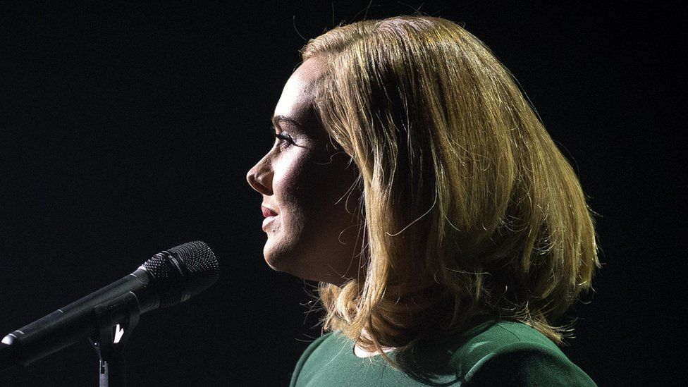 Adele stands next to a microphone ready to sing