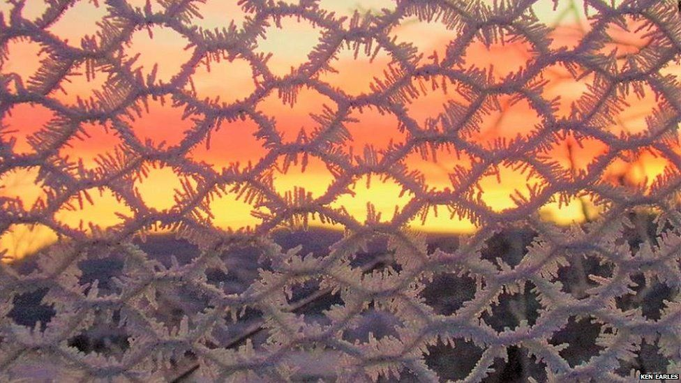 Hoar frost coated fence as the sun rises in the distance