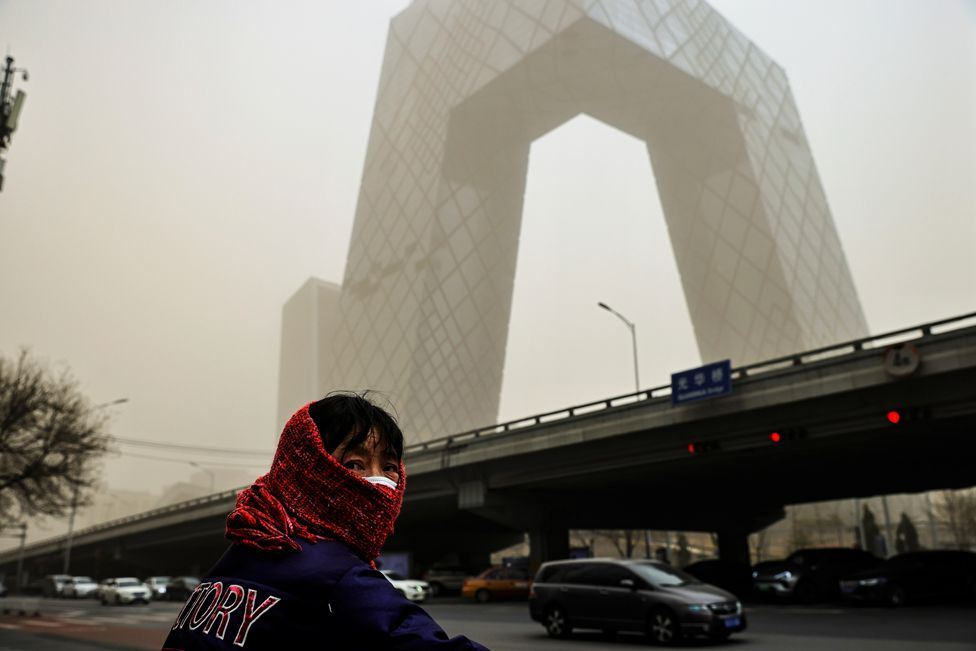 A woman wearing a head covering is seen in front of the headquarters of China's state media broadcaster CCTV that is shrouded in haze after a sandstorm in the Central Business District of Beijing, on 15 March 2021