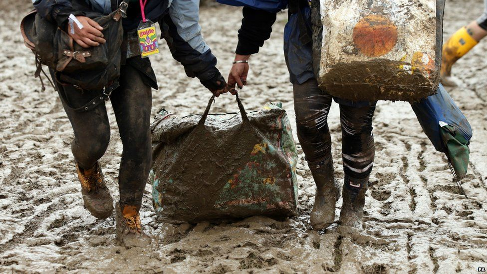 People dragging a bag through the mud