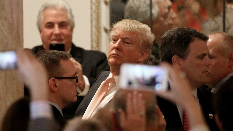 Mobile phones held up in front of Donald Trump