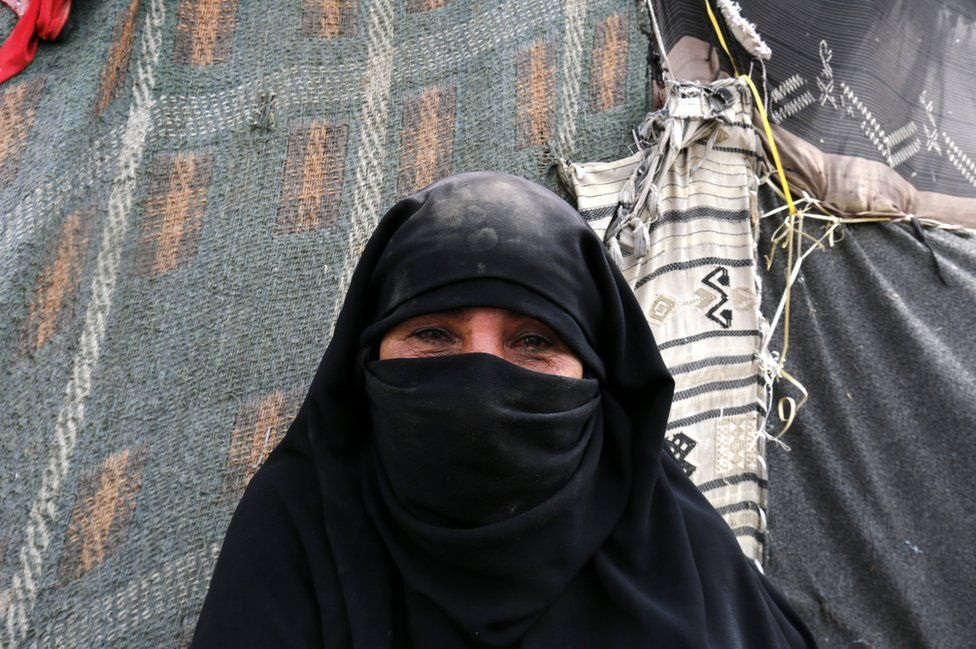 Through her veil a woman's eyes are full of tears