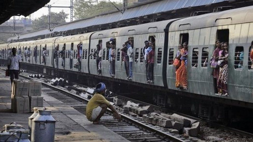 Indian passengers hang from the doors of the coaches of a crowded local train on the outskirts of Kolkata, India, Thursday, Feb. 26, 2015