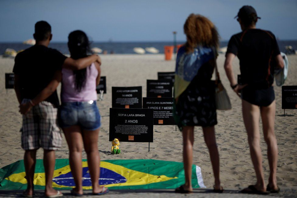 Signs that bear the names of children killed by stray bullets are seen during a protest calling for an end to the violence that erupts during police operations against suspected drug traffickers and thieves, at the Copacabana beach in Rio de Janeiro