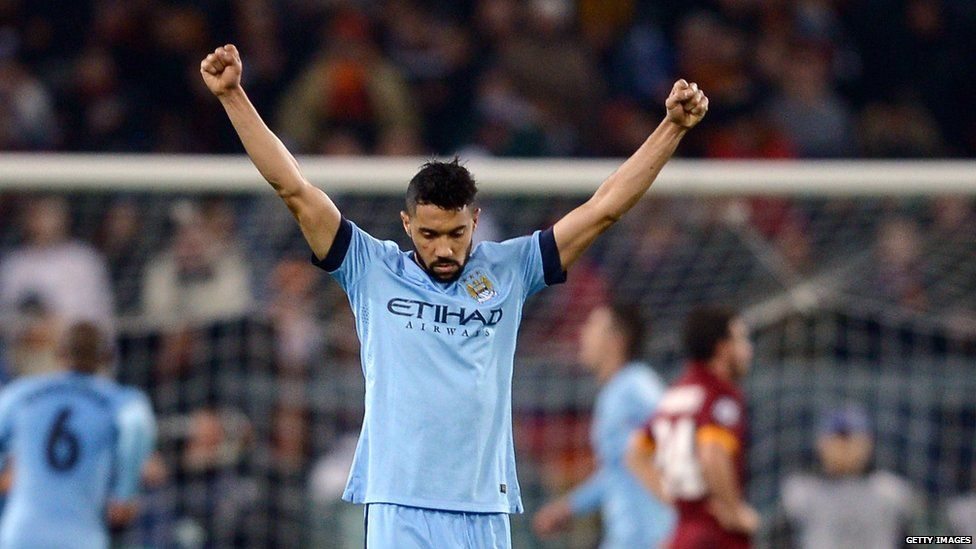 Manchester City defender Gael Clichy holds his arms aloft to celebrate victory