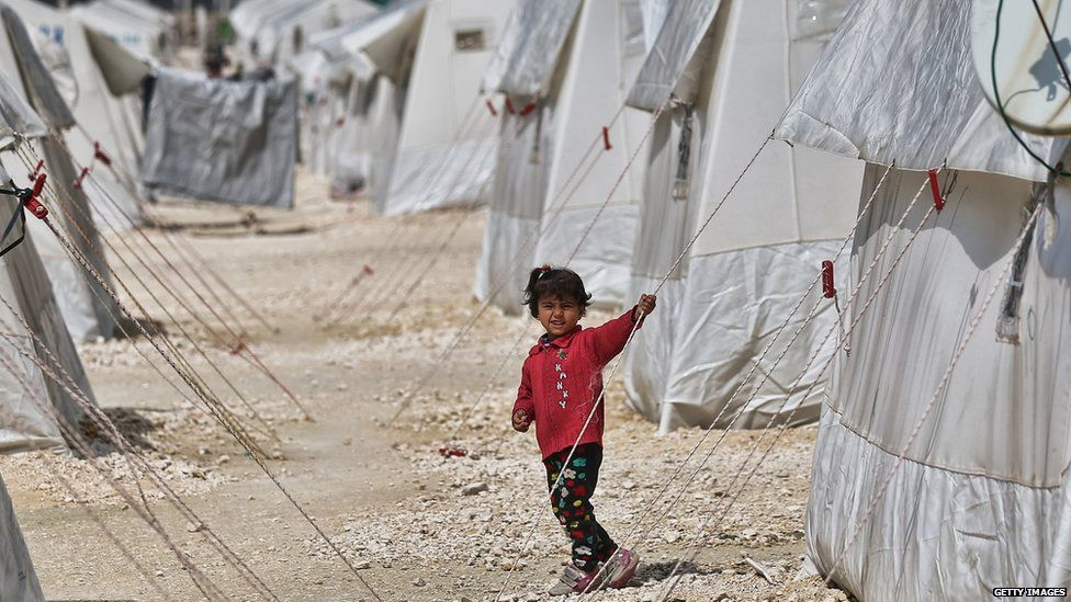 A Syrian child walks between tents in Suruc refugee camp
