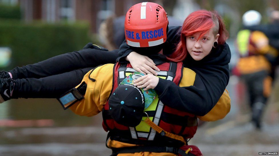 A member of rescue team helps a young woman in Carlisle