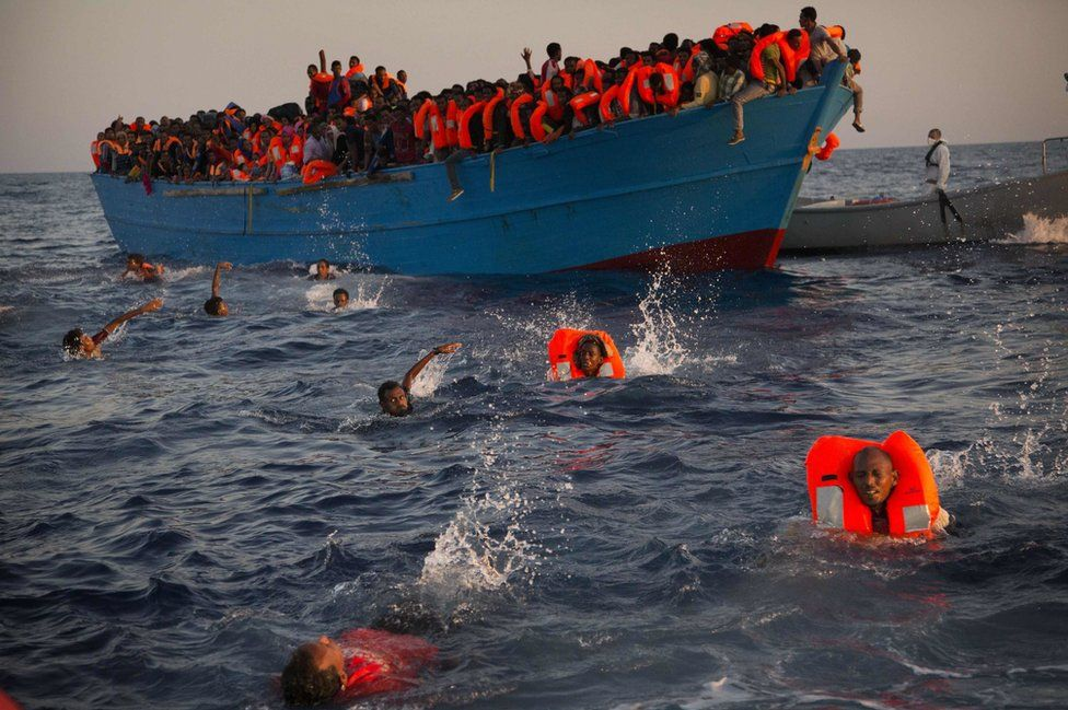 Migrants, most from Eritrea, jump into the water from a crowded wooden boat as they are helped by members of an NGO during a rescue operation in the Mediterranean sea, about 13 miles north of Sabratha, Libya, on 29 August 2016.