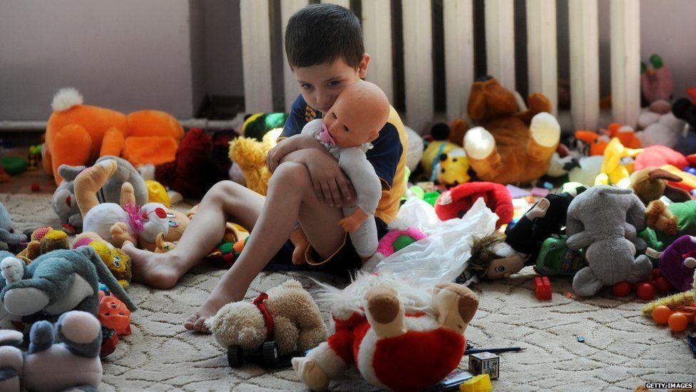 A young boy cuddling a doll