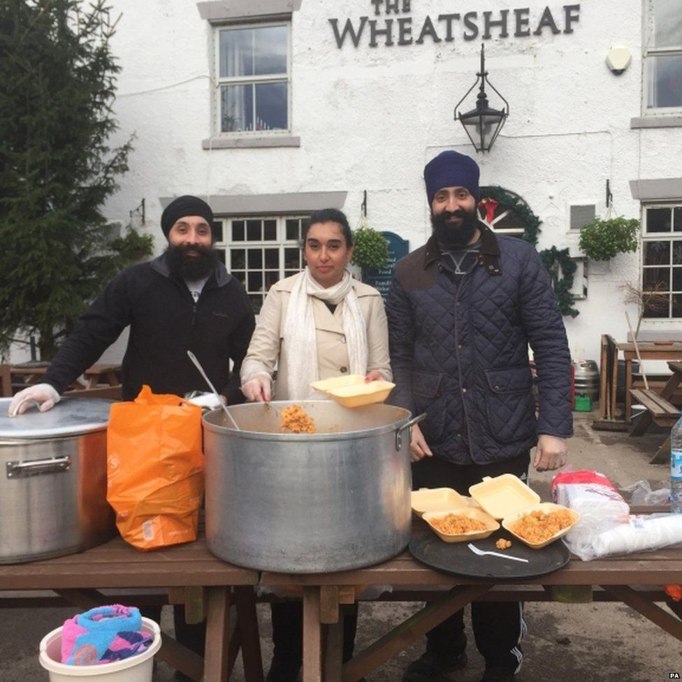 Jarnail Singh, Rani Singh and Gopal Singh, volunteers with Khalsa Aid who have been giving out food to villagers in the flood-hit Lancashire village of Croston