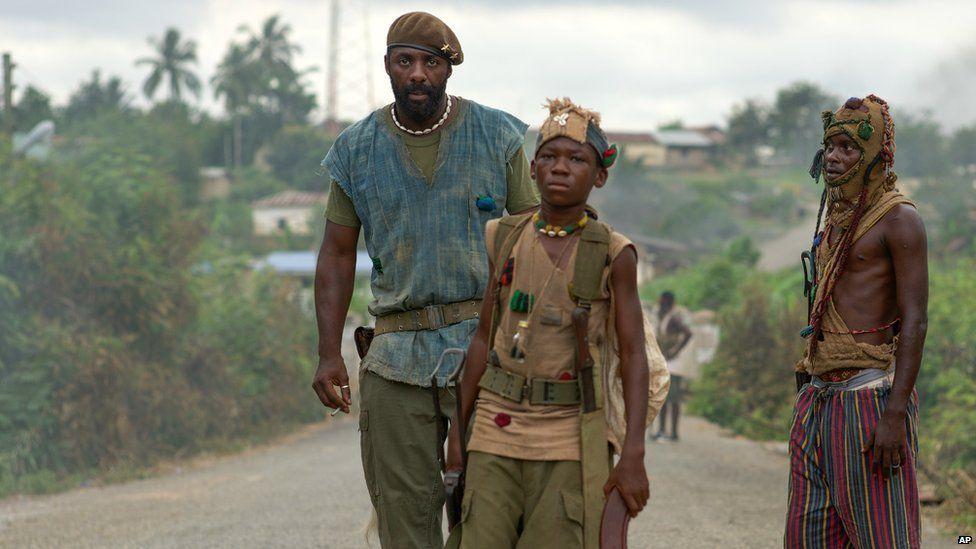 Idris Elba, left, as Commandant, and Abraham Attah, center, as Agu,