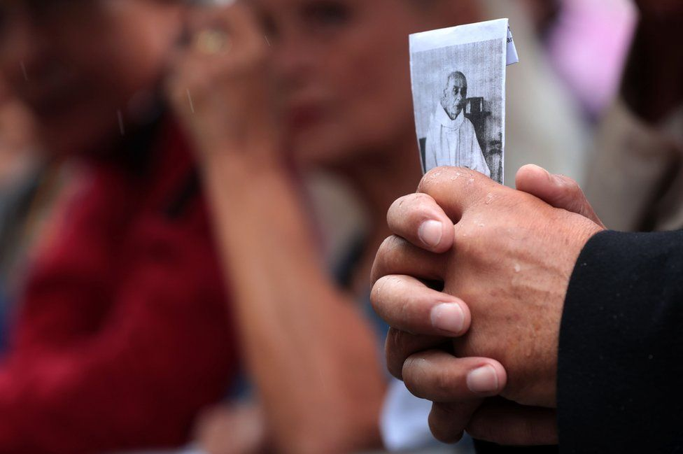 A man holds a picture of the priest Jacques Hamel outside Rouen's cathedral