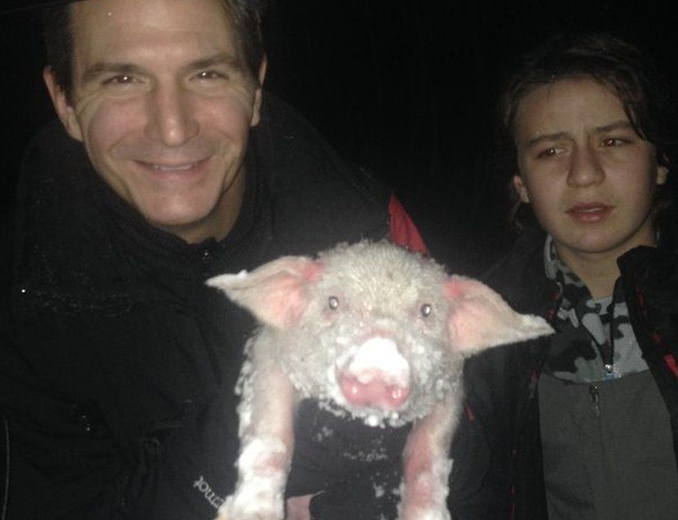 Perry Smith and his son with an icy piglet