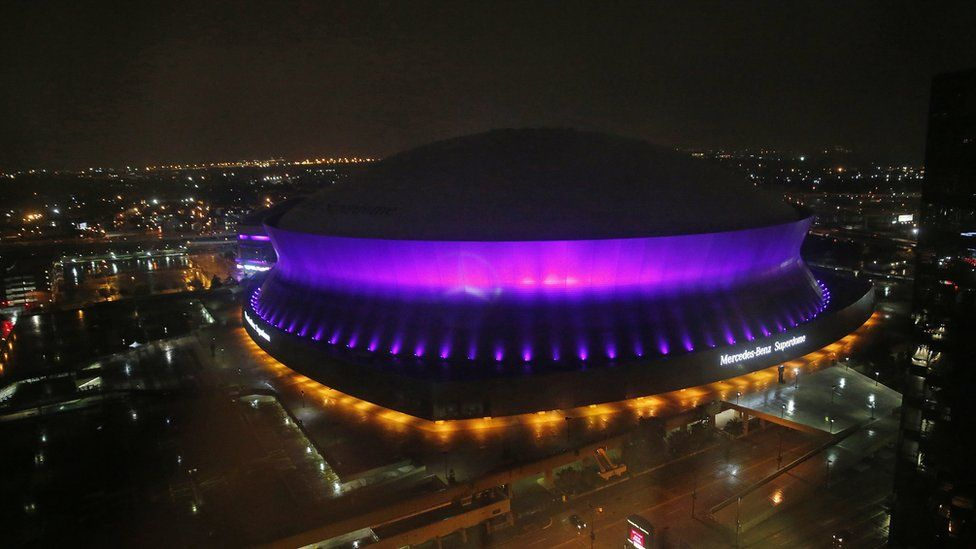 The Mercedes-Benz Superdome is lit up purple in New Orleans