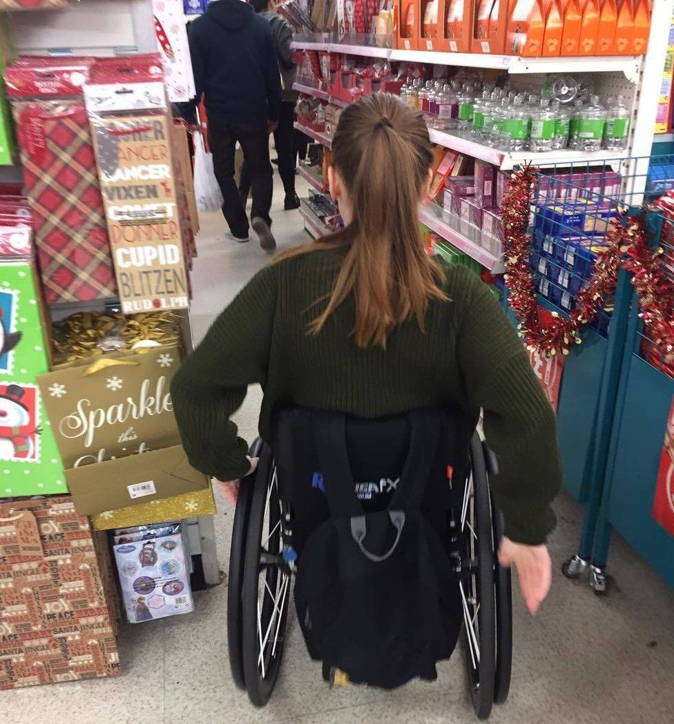 Charlotte trying to squeeze through a narrow aisle in her wheelchair