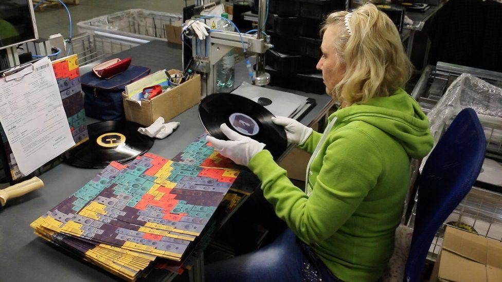 A vinyl record is quality checked in the packaging room