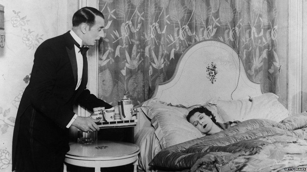Black and white photo of a butler bringing drinks to a sleeping woman