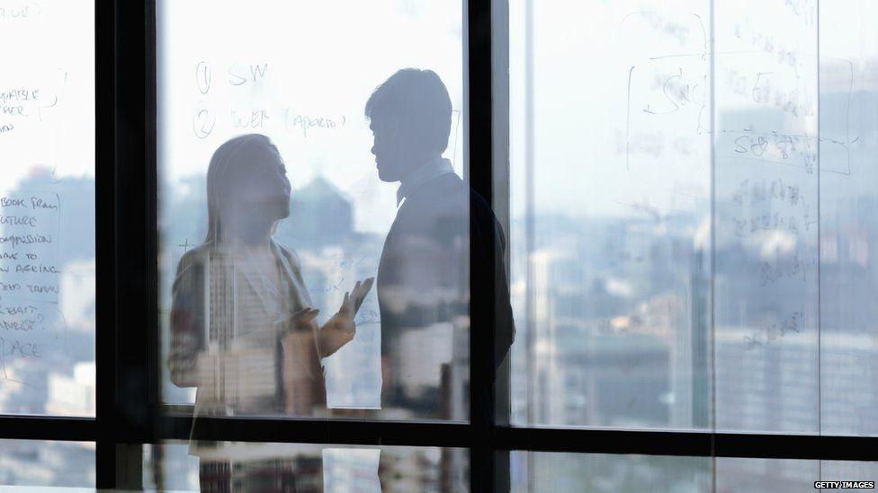 A woman and man talk at work