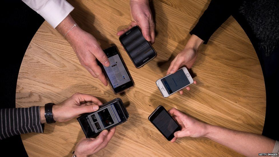 Hands and phones around a round table