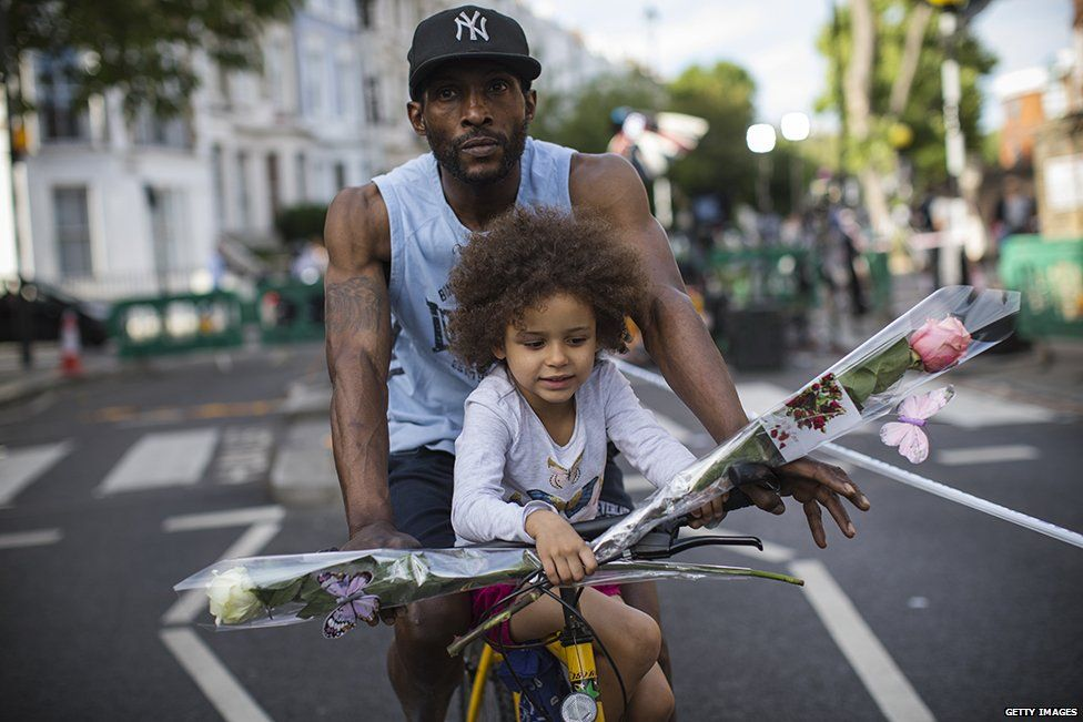 A nearby resident and his daughter bring flowers on a bike