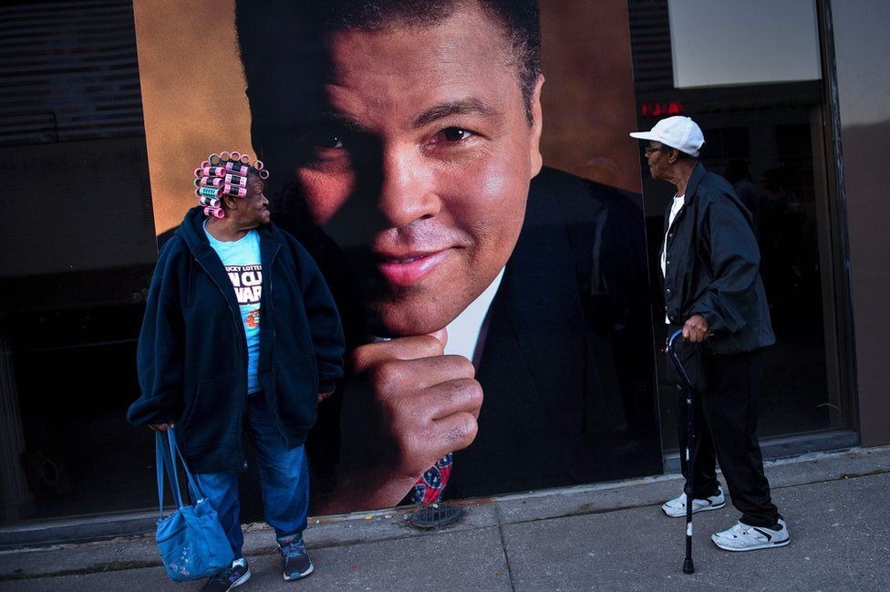 Arvetta Barbour and Lillie Burney look at a large photo of boxing legend Muhammad Ali in Louisville, Kentucky