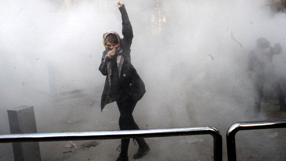 An Iranian woman raises her fist amid the smoke of tear gas