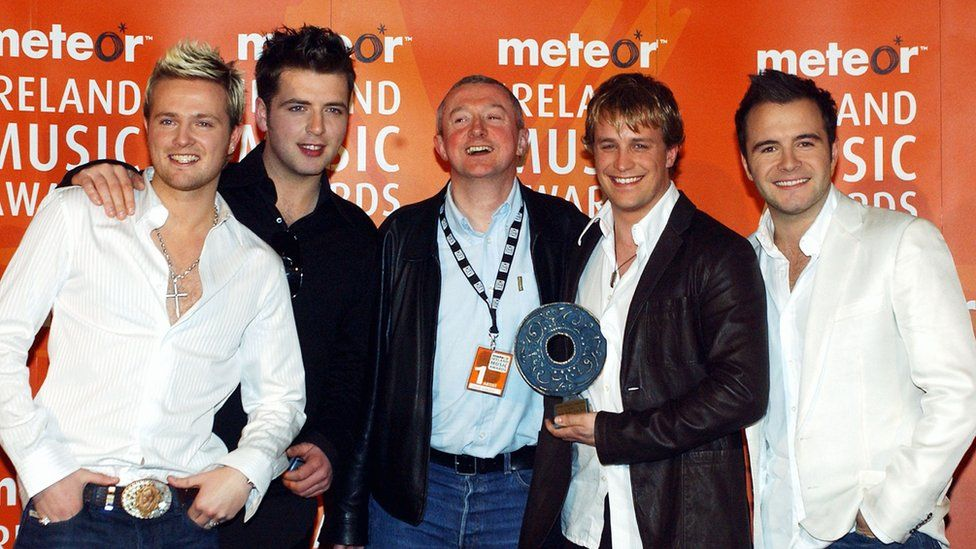 This is a photo of Louis Walsh with boyband Westlife.