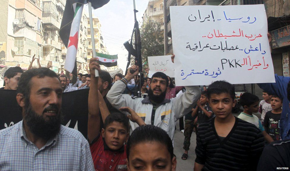 Residents carrying Free Syria Army flags and a weapon chant slogans as they protest against Russian airstrikes in Syria, in Aleppo