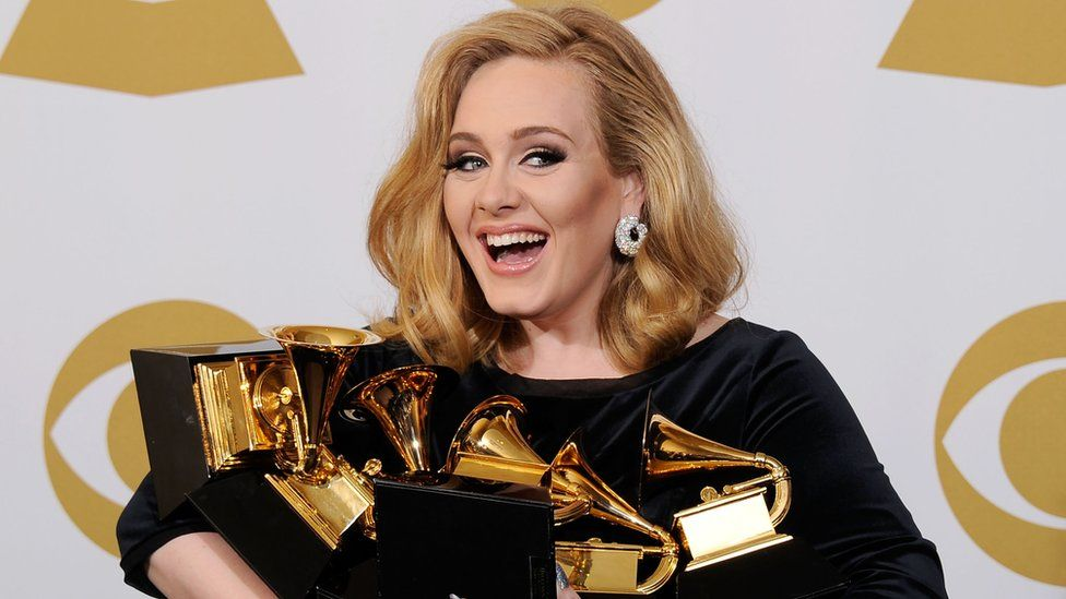 This is a photo of singer Adele holding her Grammy awards.