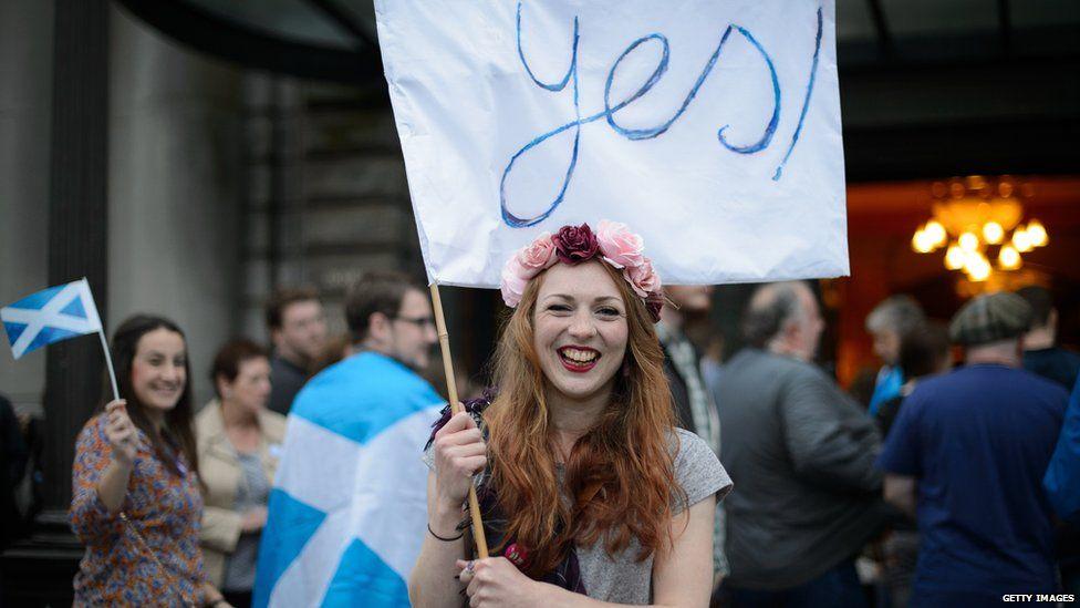 Scottish voter holding 'yes' flag