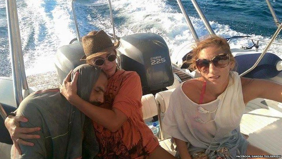 Sandra Tsiligeridu and a friend with a Syrian refugee they'd founf in the water