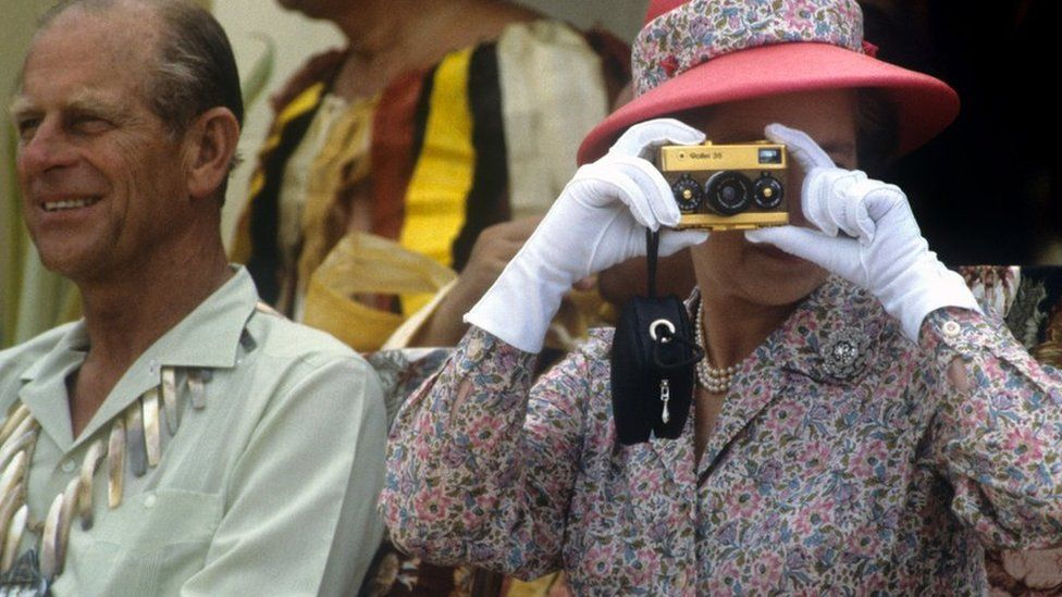 The Queen in Tuvalu in 1982 with the Duke of Edinburgh. She is taking a picture using a disposable camera.