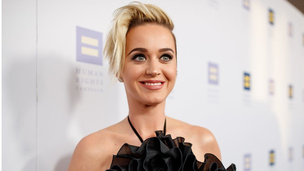 This is a photo of Katy Perry smiling on a red carpet.