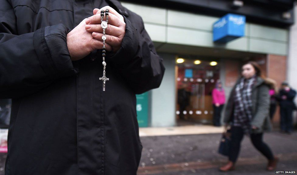 An anti-abortion activist prays with his rosary beads outside the Marie Stopes Clinic on January 12, 2016 in Belfast, Northern Ireland.