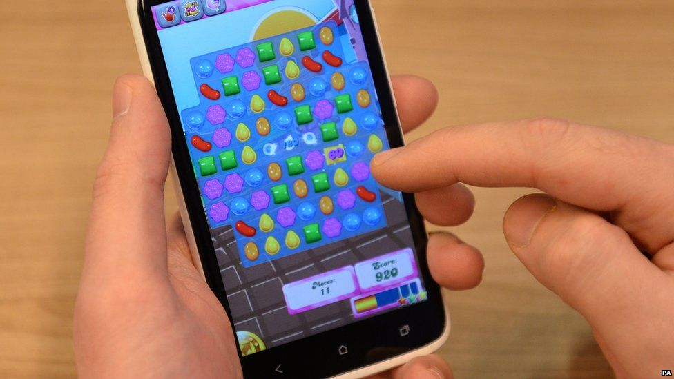 Hands holding a phone with Candy Crush loaded on it