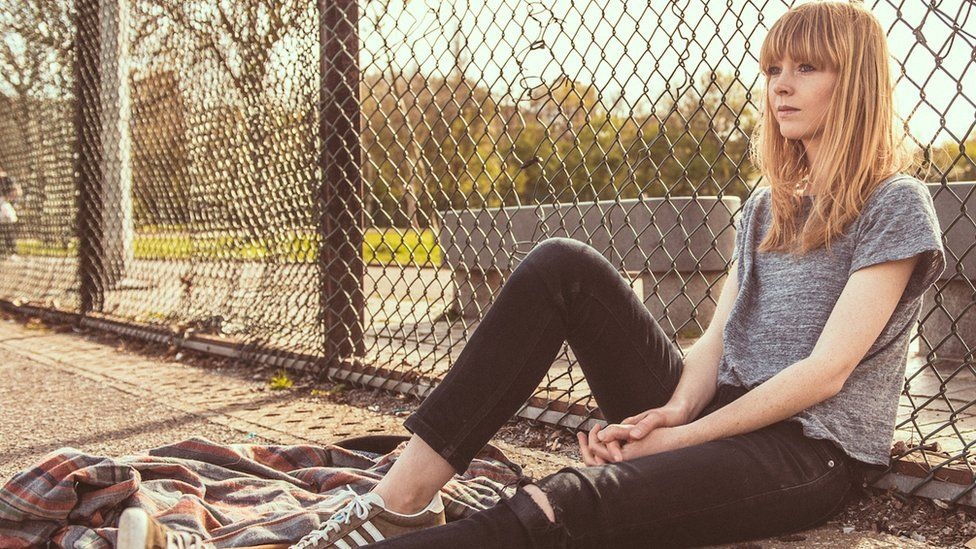 Lucy Rose sitting by a fence